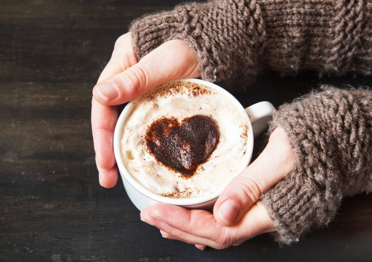 Hands Holding Warm Cappuccino with Froth and Cocoa Heart Shape